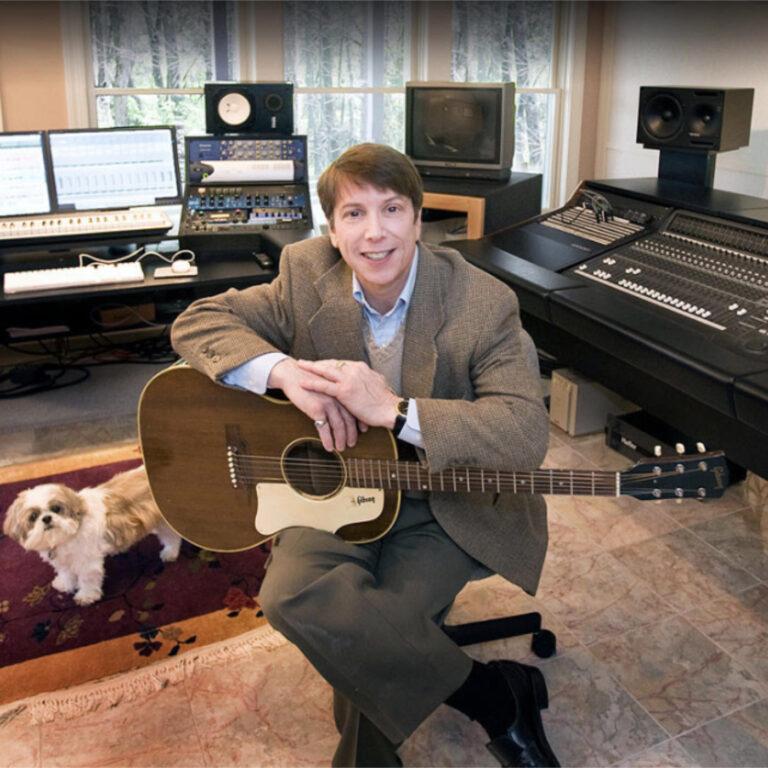 Dennis Scott with guitar in his studio